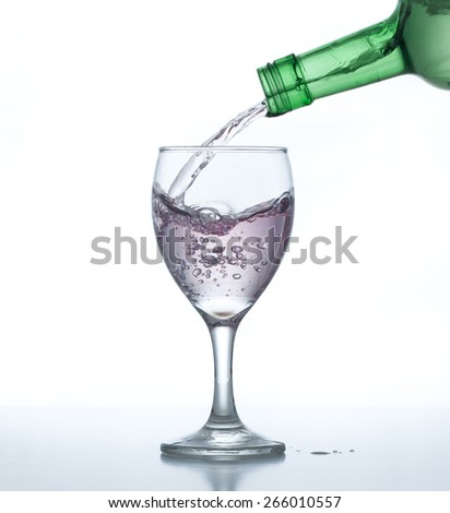 Liquor pouring into wine glass on reflective table with white background. - stock photo