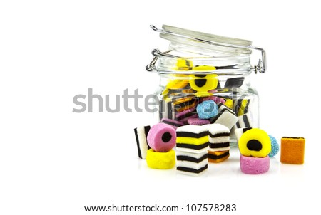 Liquorice allsort sweets in storage jar isolated over white background. - stock photo