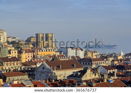 Lisbon cathedral, city roofs and bulk-carrier ship in the sea - stock photo