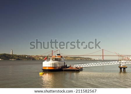 LISBON, Circa August 2014: A ferry boat and a pier on the River Tagus, the longest river in the Iberian Peninsula. August 2014 in Lisbon, Portugal  - stock photo