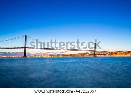 Lisbon cityscape with 25 de Abril suspension Bridge, Portugal sunset - stock photo