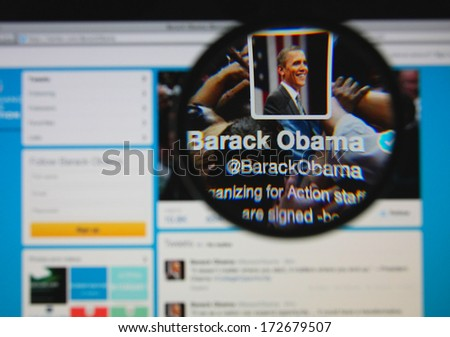 LISBON - JANUARY 22, 2014: Photo of Barack Obama's official twitter page on a monitor screen through a magnifying glass. - stock photo