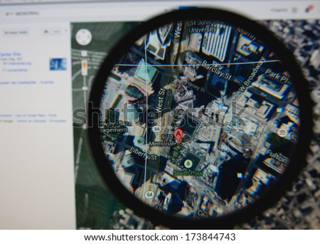 LISBON - JANUARY 29, 2014: Photo of Google Maps pinpointing the 9/11 Memorial on a monitor screen through a magnifying glass. - stock photo