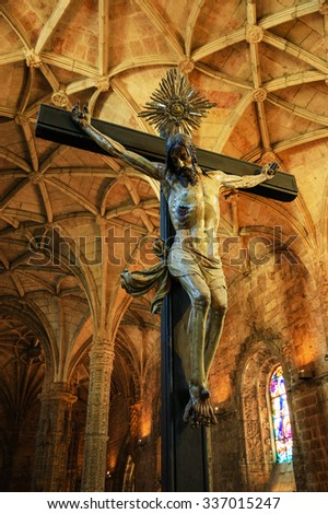 LISBON, PORTUGAL - APRIL 22, 2015: Crucifix and ceiling inside the church of Jeronimos Monastery. This monastery is one of the most prominent examples of the Portuguese Gothic Manueline style. - stock photo