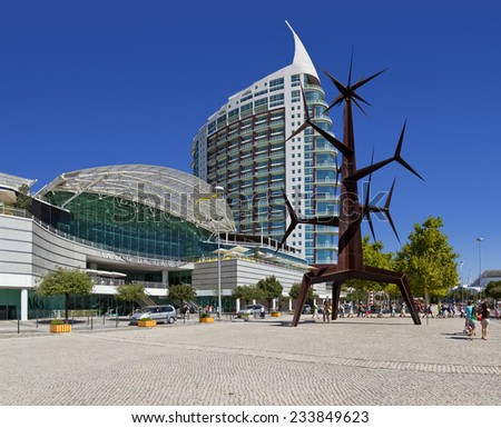 Lisbon, Portugal - August 02, 2013: Visitors comming in and out of the Vasco da Gama Shopping, Sao Rafael Tower in the back and Homem-Sol (Sun-Man) Sculpture. Parque das Nacoes. - stock photo