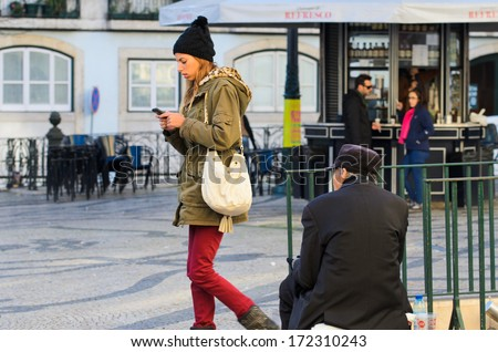 LISBON, PORTUGAL - DECEMBER 5, 2013: A young woman, handling a mobile phone, passes indifferent to a homeless begging on the streets of Lisbon. - stock photo