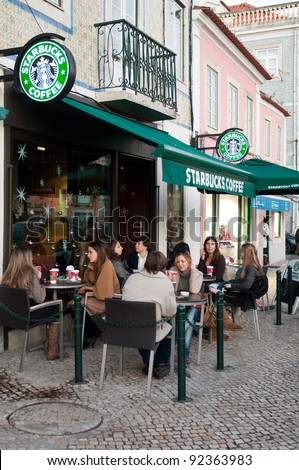 LISBON, PORTUGAL - DECEMBER 19: people having a break at Starbucks coffee esplanade on December 19, 2011 in Lisbon, Portugal. The largest coffeehouse company in the world with 18,887 stores - stock photo