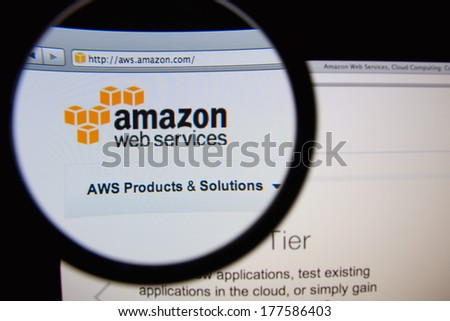LISBON, PORTUGAL - FEBRUARY 19, 2014: Amazon Web Services homepage through a magnifying glass. AWS is a collection of web services that together make up a cloud computing platform. - stock photo