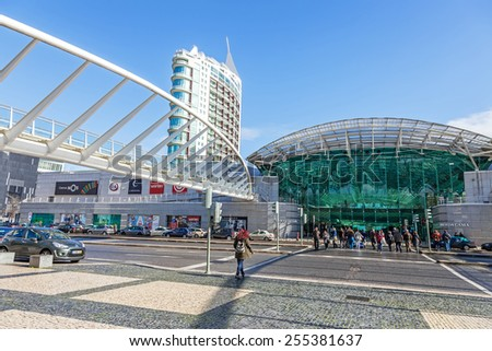 Lisbon, Portugal - February 01, 2015: People crossing the road in front of the Vasco da Gama Shopping Centre entrance. Parque das Nacoes (Park of Nations). - stock photo