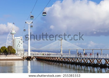 Lisbon, Portugal - February 01, 2015: People practicing sports on the Passeio Ribeirinho over the Tagus River. Vasco da Gama Tower and Bridge, Myriad Hotel and aerial tramway. Park of Nations - stock photo
