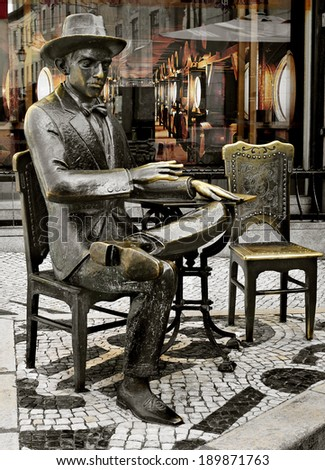LISBON, PORTUGAL - MARCH 18: Statue of Fernando Pessoa outside of Cafe A Brasileira on March 18, 2014 in Lisbon, Portugal. This iconic statue and the cafe itself are visited for thousands of tourists - stock photo