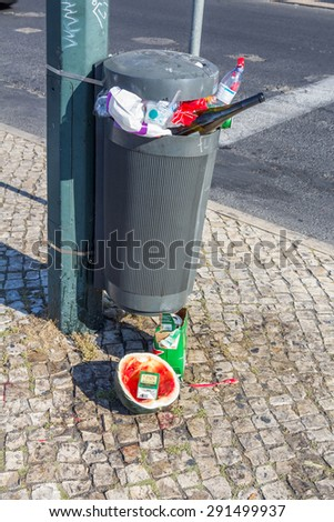 LISBON, PORTUGAL - MAY 24, 2015: A garbage bin full of garbage found in a roadside of Lisbon, the capital of Portugal. - stock photo