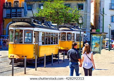 LISBON, PORTUGAL - MAY 3rd, 2016 : Couple holding hands passing in Alfama district in Lisbon with two yellow trams on the background.  - stock photo