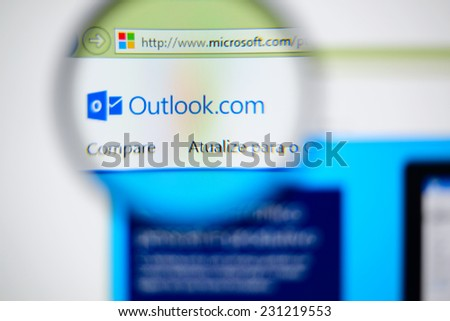LISBON, PORTUGAL - NOVEMBER 17, 2014: Photo of Outlook homepage on a monitor screen through a magnifying glass. - stock photo