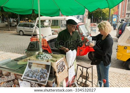 LISBON, PORTUGAL - OCTOBER 19, 2015: A typical chestnut vendor in the streets of Lisbon offering freshly roasted chestnuts to tourists and inhabitants of the Portuguese capital. - stock photo