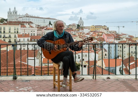 LISBON, PORTUGAL - OCTOBER 18, 2015: Typical Fado musician singing to his guitar in front of the district of Alfama, the oldest district of Lisbon with many Fado bars and musicians performing the - stock photo