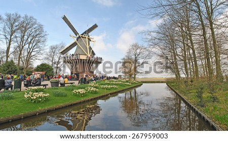 LISSE, THE NETHERLANDS, 08 APRIL 2015 - Windmill and water in Keukenhof, Lisse, The Netherlands. Keukenhof is the biggest flower park in the world. - stock photo