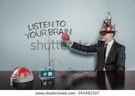 Listen to your brain concept with businessman holding brain at hand in office - stock photo