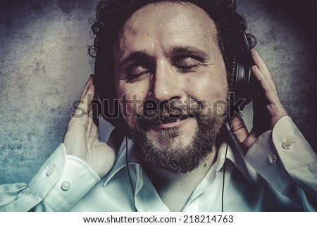 listening and enjoying music with headphones, man in white shirt with funny expressions - stock photo
