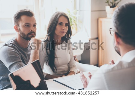 Listening to financial advisor. Concentrated young couple bonding to each other and listening to some man sitting in front of them at the desk in office - stock photo