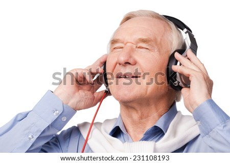 Listening to his favorite music. Portrait of cheerful senior man in headphones listening to music and keeping eyes closed while standing against white background  - stock photo