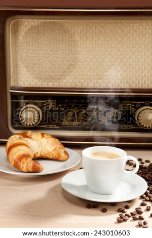 Listening to the radio at breakfast with coffee and croissant - stock photo