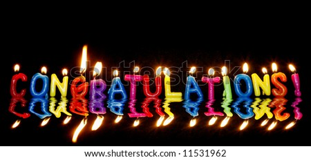 lit candles spelling congratulations with reflection - stock photo