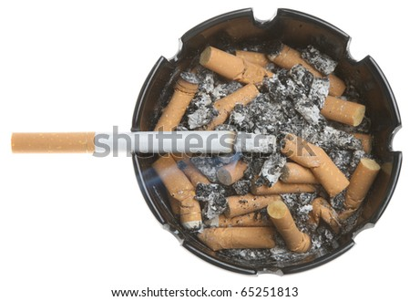 Lit cigarette in a full ashtray. - stock photo