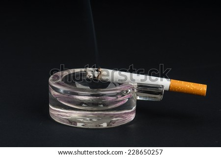 Lit cigarette in a glass ashtray on black background - stock photo