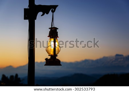 Lit lantern at sunset, Himalayas in the background, in Nepal - stock photo
