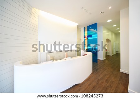 Lit reception area in dental clinic. Working place - table with computer. - stock photo