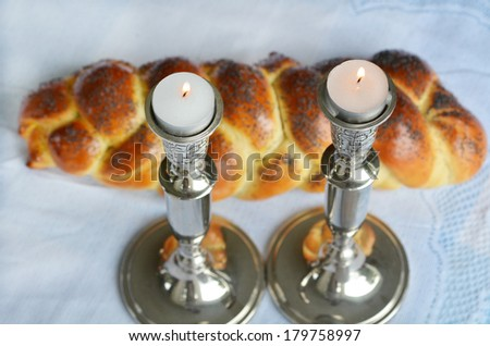 Lit Shabbath candles with uncovered challah bread and kippah. - stock photo