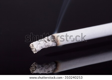 lit single cigarette with smoke isolated on black background -macro - stock photo