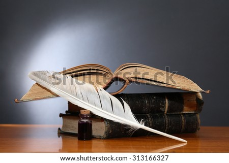 Literature concept. Still life with quill pen near book on wooden table - stock photo