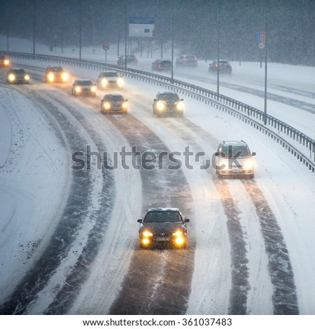 LITHUANIA, VILNIUS - JAN 11, 2016: Traffic in Vilnius during winter snowstorm. Roads slippery with snow or ice can cause vehicles to go out of control easily. - stock photo