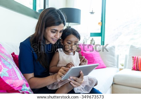 Litlle girl play tablet pc with her mother at home - stock photo
