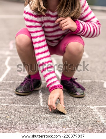 Litlle girl playing on the hopscotch - stock photo