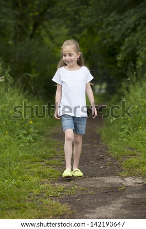 Litte girl walking on a path in the woods - stock photo