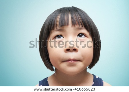 Littel cute girl looking up - stock photo
