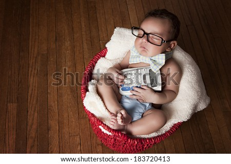 Little Accountant.  Adorable newborn wearing glasses and a bow-tie and holding a calculator.  Room for your text! - stock photo