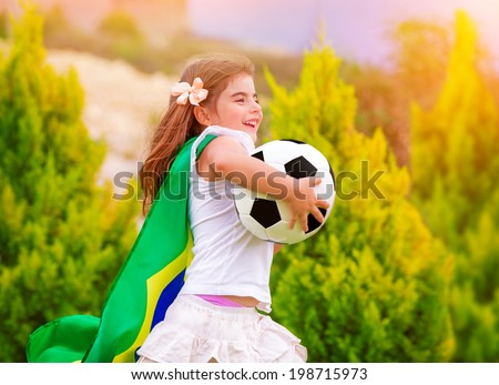 Little active football fan running on the green grass field with ball, young supporter of Brazilian football team with national flag  - stock photo