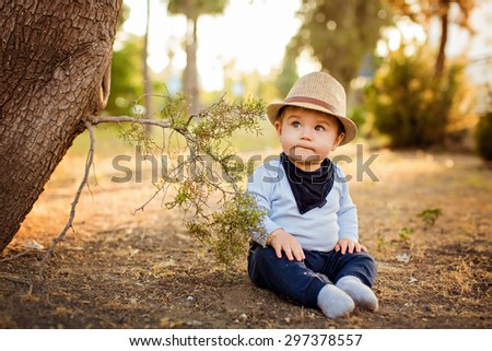 Little adorable baby boy in a straw hat and blue pants sitting with pursed lips, near a tree on earth at sunset in summer - stock photo