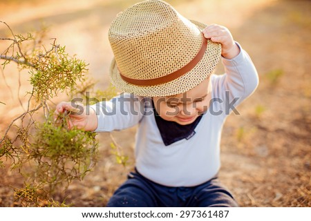 Little adorable baby boy in a straw hat and blue shirt sitting near a tree on the ground at sunset in the summer, and tries to take off his hat - stock photo
