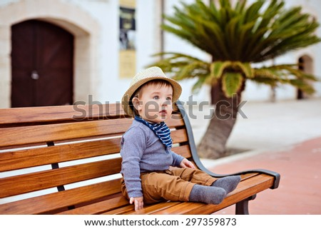 Little adorable baby boy in a straw hat and brown pants sitting on a bench on the background of palm trees, summer - stock photo