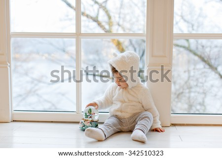Little adorable boy baby clothing white teddy bear sitting near the window, holding a ball in the interior of the house - stock photo