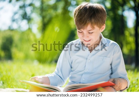Little adorable boy in sitting park with book in hands - stock photo