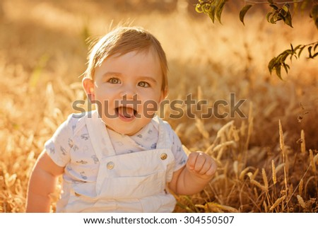 Little adorable chubby baby boy sitting in a white jumpsuit in the field in the spikelets in the warm rays of the setting sun in the summer, fun smiles - stock photo