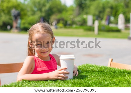 Little adorable girl at outdoor cafe on warm summer day - stock photo
