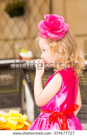 Little adorable girl celebrating 3 years birthday.  Kid  wearing flower hairband on party outdoors on summer day. Childhood. - stock photo