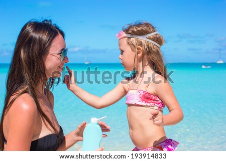 Little adorable girl gets sun cream on her mother's nose - stock photo